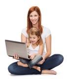Madre feliz con la niña y el ordenador portátil adorables Imagen de archivo libre de regalías