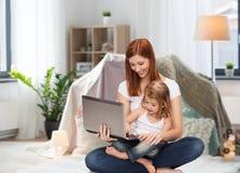Madre feliz con la pequeños hija y ordenador portátil Fotografía de archivo libre de regalías
