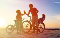 Madre feliz con los niños biking en la puesta del sol Fotografía de archivo