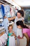 Madre feliz con los pijamas de compra del bebé de la hija en la sección de los niños Fotos de archivo libres de regalías