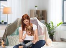 Madre feliz con pequeña PC de la hija y de la tableta Imagen de archivo libre de regalías