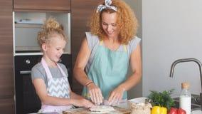 Madre feliz con poca hija en la cocina casera almacen de video