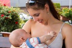 Madre feliz con sonrisa en su cara y expresión alegre que detienen a su bebé, mirándolo su y amamantando en calle pública imagen de archivo libre de regalías