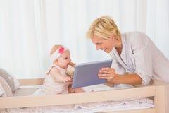 Madre feliz con su bebé que usa la tableta digital Imágenes de archivo libres de regalías