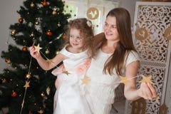 Madre feliz con su guirnalda de la Navidad del control de la hija de estrellas en sus manos Imagen de archivo