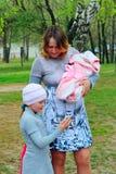 Madre feliz con su más vieja mirada de la hija a través de la foto del bebé recién nacido Fotografía de archivo