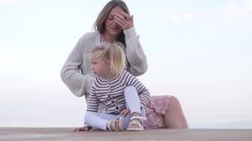 Madre feliz con su pequeña hija que se sienta en la playa en la puesta del sol almacen de video