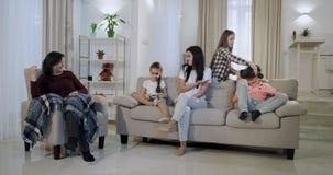 Madre feliz con sus niños y una abuelita que pasa una época junta en la sala de estar ellos que juegan en un virtual metrajes