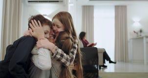 Madre feliz con sus tres niños que abrazan junto como un equipo amistoso en tabla de la sala de estar, mientras que lectura a de  almacen de video