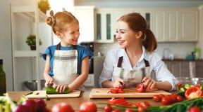 Madre feliz de la familia con la muchacha del ni?o que prepara la ensalada vegetal fotos de archivo libres de regalías