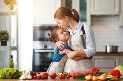 Madre feliz de la familia con la muchacha del ni?o que prepara la ensalada vegetal imágenes de archivo libres de regalías