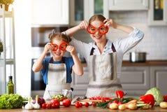 Madre feliz de la familia con la muchacha del ni?o que prepara la ensalada vegetal fotos de archivo