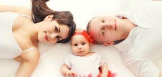 Madre feliz de la familia del primer del retrato, padre con el bebé que miente en cama o alfombra en casa fotografía de archivo