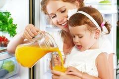 Madre feliz de la familia e hija del bebé que bebe el zumo de naranja adentro Fotos de archivo libres de regalías