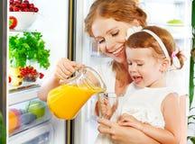 Madre feliz de la familia e hija del bebé que bebe el zumo de naranja adentro Fotografía de archivo