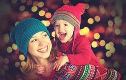 Madre feliz de la familia y pequeña hija que juegan en el invierno para la Navidad