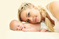 Madre feliz del retrato con el bebé que miente en hogar de la cama junto Imagen de archivo libre de regalías