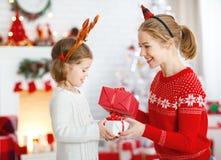 Madre feliz e hija de la familia que dan el regalo de la Navidad Fotos de archivo