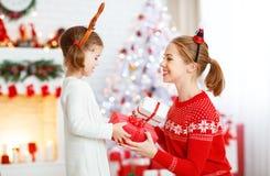 Madre feliz e hija de la familia que dan el regalo de la Navidad Imagen de archivo