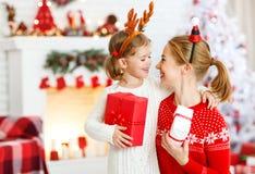 Madre feliz e hija de la familia que dan el regalo de la Navidad Imagen de archivo libre de regalías