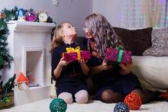 Madre feliz e hija, presentando contra la chimenea, el humor de la Navidad y del Año Nuevo imagen de archivo