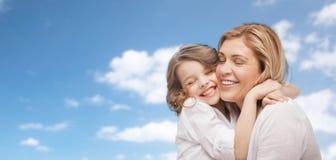 Madre feliz e hija que abrazan sobre el cielo azul Foto de archivo libre de regalías