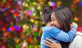 Madre feliz e hija que abrazan sobre luces Fotografía de archivo libre de regalías