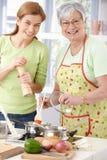 Madre feliz e hija que cocinan junto Imágenes de archivo libres de regalías