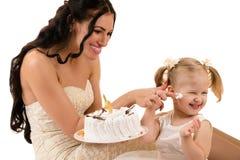 Madre feliz e hija que comen la torta en cumpleaños Foto de archivo