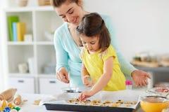 Madre feliz e hija que hacen las galletas en casa Fotografía de archivo