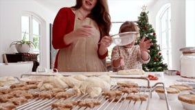 Madre feliz e hija que hacen las galletas para la Nochebuena almacen de metraje de vídeo
