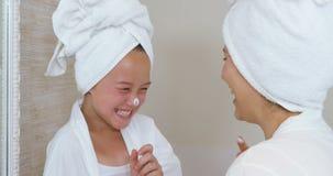 Madre feliz e hija que juegan con crema de cara almacen de metraje de vídeo