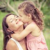 Madre feliz e hija que juegan en el parque en el tiempo del día Imagen de archivo