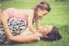 Madre feliz e hija que juegan en el parque en el tiempo del día Fotografía de archivo libre de regalías