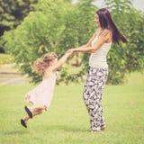 Madre feliz e hija que juegan en el parque en el tiempo del día Imagen de archivo libre de regalías