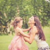 Madre feliz e hija que juegan en el parque en el tiempo del día Imágenes de archivo libres de regalías