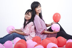 Madre feliz e hija que presentan con los globos Imágenes de archivo libres de regalías