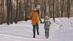 Madre feliz e hija que ríen y que saltan en bosque del invierno en la cámara lenta metrajes