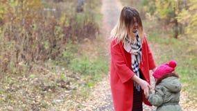 Madre feliz e hija que se divierten que juega en el parque en otoño metrajes