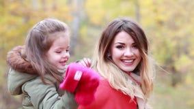 Madre feliz e hija que se divierten que juega en el paseo en día del otoño almacen de video