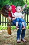 Madre feliz e hija que se sientan en el oscilación Fotos de archivo libres de regalías