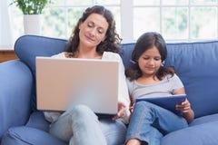 Madre feliz e hija que se sientan en el sofá mientras que usa el ordenador portátil y la tableta Imagenes de archivo