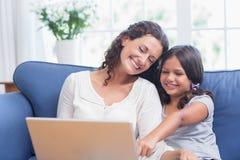 Madre feliz e hija que se sientan en el sofá y que usan el ordenador portátil Fotos de archivo