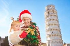 Madre feliz e hija que sostienen el árbol de navidad Pisa, Italia Foto de archivo
