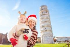Madre feliz e hija que toman la foto La Navidad en Pisa Foto de archivo libre de regalías