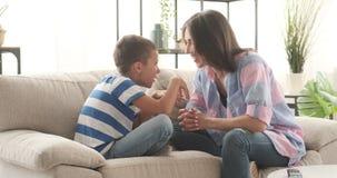 Madre feliz e hijo que hablan en el sofá en casa almacen de video