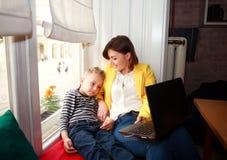 Madre feliz e hijo que miran el ordenador portátil en casa Imágenes de archivo libres de regalías