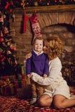madre feliz e hijo que se sientan cerca de un árbol de navidad y de una chimenea Fotos de archivo