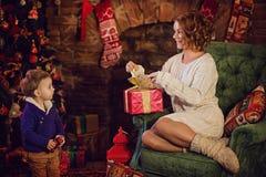 madre feliz e hijo que se sientan cerca de un árbol de navidad y de una chimenea Imagen de archivo