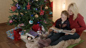 Madre feliz e hijo que se sientan debajo de un árbol de navidad y que mueven de un tirón el álbum de foto almacen de metraje de vídeo